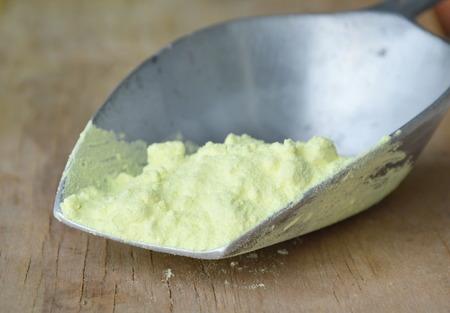 sulphur powder on iron scoop