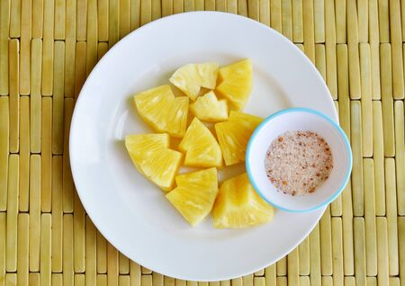 digest: pineapple slice dipping with mixed sugar salt and pepper on white plate