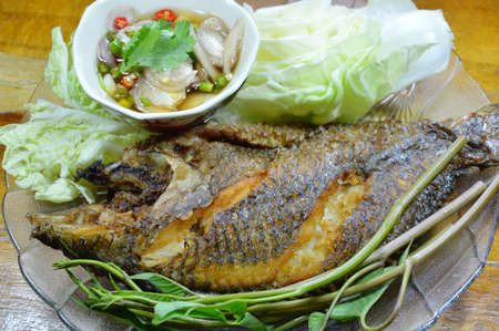 mango fish: deep fried mango fish dipping chili fish sauce and vegetable on dish