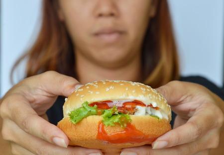 varkensvlees hamburger dressing tomatensaus op vrouwenhand
