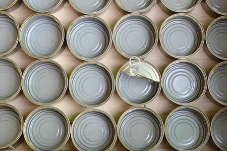 food can: empty tin food can in brown paper box Stock Photo