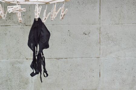 brassiere: old black brassiere hanging on white clothespin in backyard garden Stock Photo