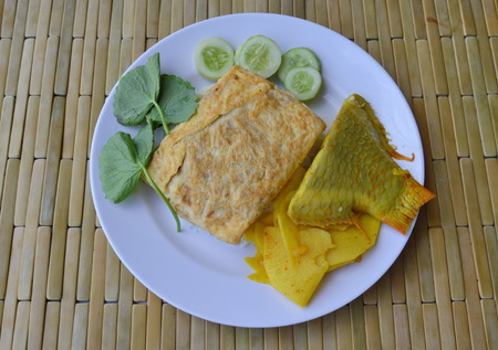 mango fish: fried egg and pickled bamboo shoot mango fish curry on rice Stock Photo