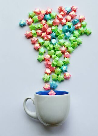 fling: colorful star paper splashing from coffee cup on white background