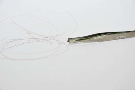 pinzas: pinzas de plata y el pelo en el fondo blanco Foto de archivo