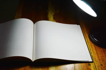 electric material: white paper book and reading lamp on wooden table in the night