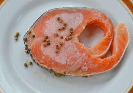 defrost: raw frozen salmon dressing pepper on plate