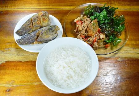 basil  leaf: boiled rice eat with stir fried crispy basil leaf with black preserved egg and deep fried fish