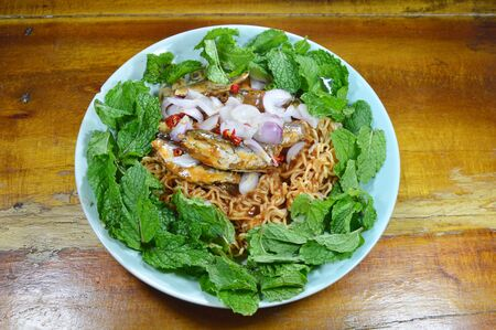 sardine can: spicy instant noodle with fish canned salad on plate