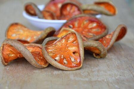 dried bael fruit on wooden board