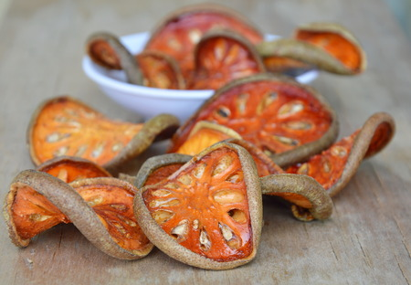 dry bael fruit on wooden board