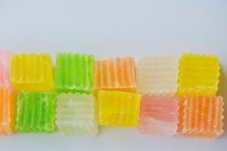 Caramelos crujientes de colores en el plato blanco