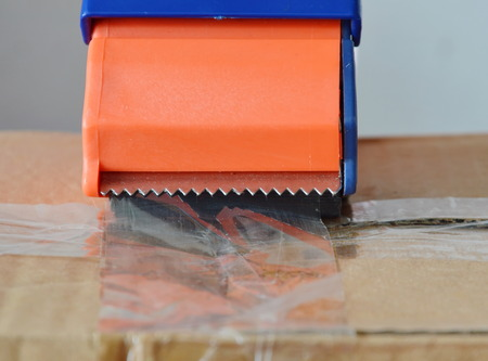 brown box: tape disperser seal brown box on for sending Stock Photo