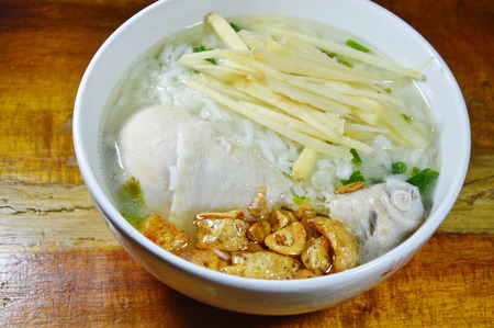 rice porridge with chicken leg topping slice ginger and fried garlic on bowl