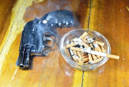 revolver gun and cigarette in glass ashtray on wooden table