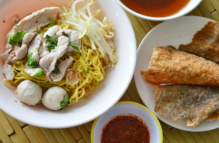 fish skin: yellow noodle topping pork ball and crispy fish skin with soup Stock Photo
