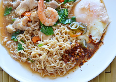 instant noodle dressing seafood gravy sauce and egg on plate Stock Photo