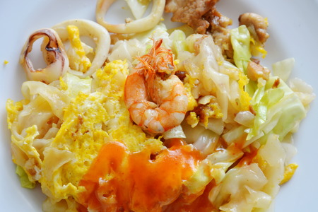 stir fried large noodle seafood and egg dressing chili on plate