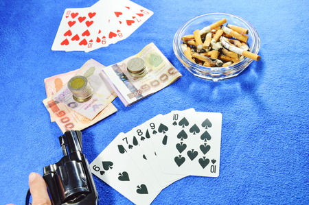 rival: hand point gun for threaten rival after win poker game Stock Photo