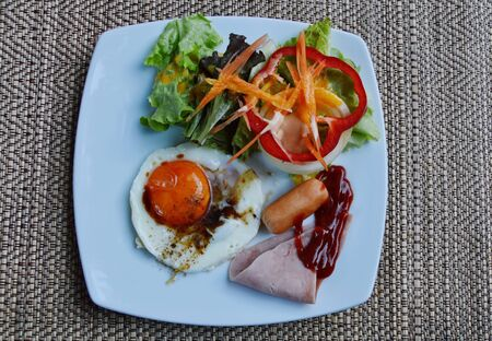 mayonesa: fried egg dressing soy sauce with pork sausage and salad on square plate Foto de archivo