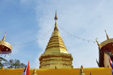 golden pagoda contain Buddha ash entwined praying cloth in Wat Phrathat Doi Kham ancient temple in Thailand Stock Photo