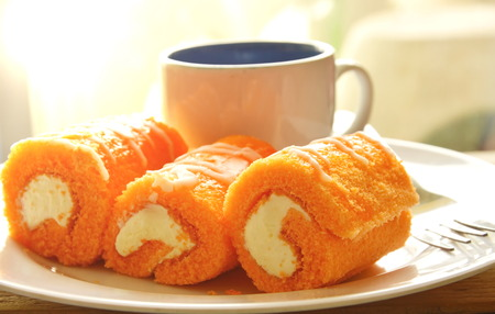 filled roll: orange cake roll filled cream eat couple with coffee on dish Stock Photo