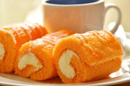 orange cake roll stuffed cream eat couple with coffee on dish