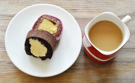 filled roll: chocolate and grape jam roll filled cream eat couple with coffee in red cup Stock Photo