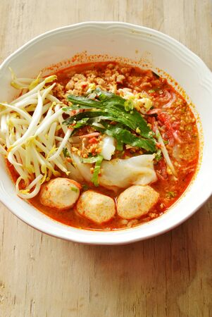 rice noodle with pork ball in tom yum spicy soup topping fresh bean sprout on bowl