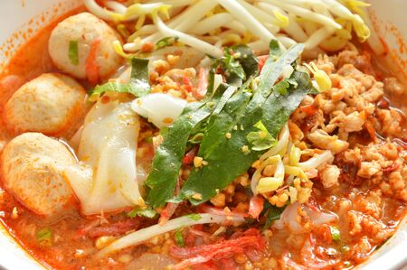large noodle with pork ball in tom yum spicy soup topping fresh bean sprout on bowl