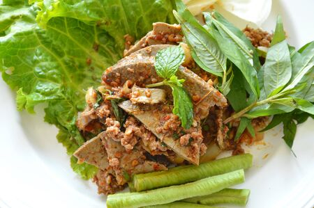 chitterlings: spicy chop pork and liver salad eat couple with fresh vegetable on plate