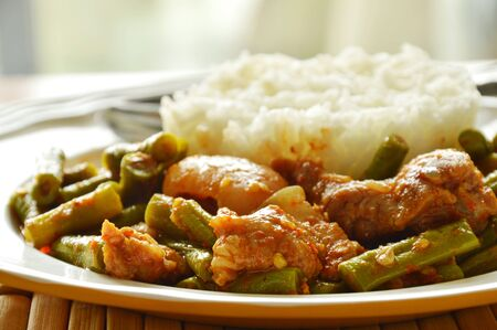 long bean: spicy stir fried fat pork and yard long bean curry eat couple with rice Stock Photo