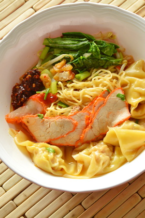 crackling: Chinese yellow noodle topping slice barbecue pork and dumpling in soup Stock Photo