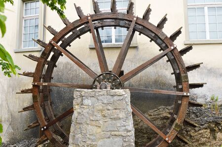 water wheel: wooden water wheel beside house in Rhine Switzerland