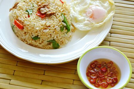 spicy fried rice pork and basil leaf topping fried egg with chili fish sauce Stock Photo