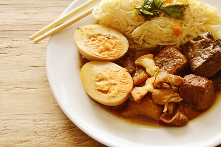 thin rice noodle with pork entrails and tofu topping egg on plate Stock Photo