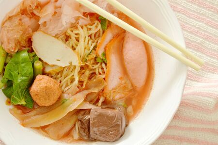 yellow noodles with squid and fish ball in red soup Chinese-language called Yong Tau Fu Stock Photo