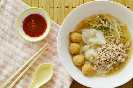 rice noodles topping boiled minced pork and shrimp ball in soup with chili sauce