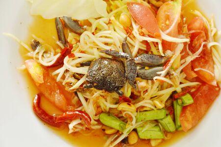 Somtum Thai papaya verde picante con ensalada de cangrejo en escabeche negro en un plato Foto de archivo