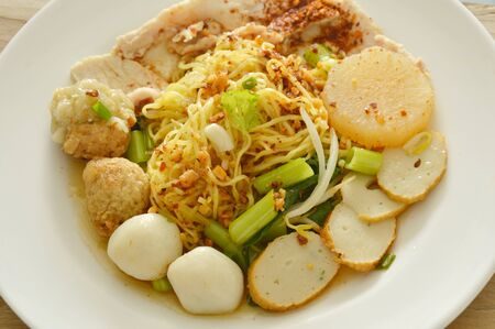 dried spicy Chinese egg noodles topping fish and shrimp ball with slice boiled pork on plate Stock Photo