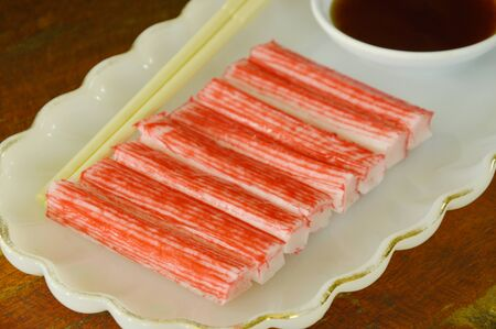 dipping: imitation crab stick made from fish with soy sauce on plate