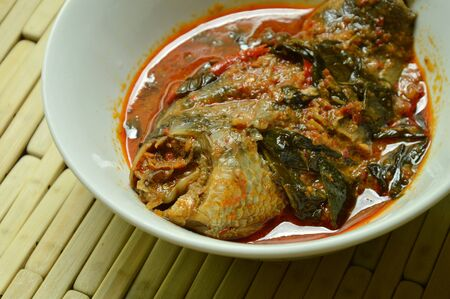 spicy climbing perch fish dried red curry paste with basil on bowl