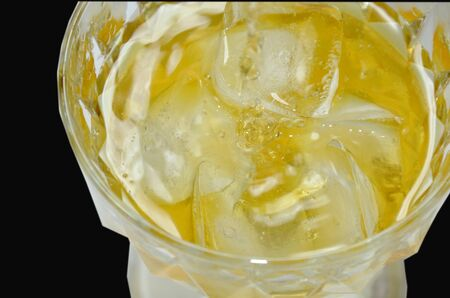 dilute: whiskey pour on ice in black background
