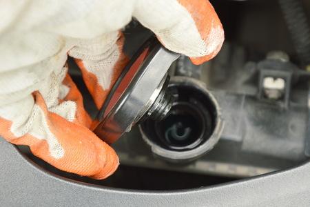 hand in handschoen open radiatorafdekking en controleer het waterniveau op veiligheid