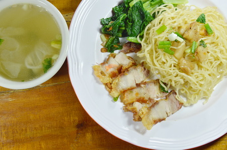 crackling: Chinese yellow noodles topping crispy pork on plate with soup