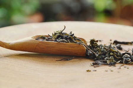dry Chinese tea leaves in wooden scoop on chop block Stock Photo