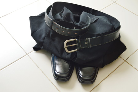 black business pant and lather shoe on white tile floor
