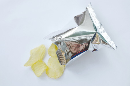 potato chip pouring from aluminium foil packaging on white background