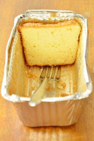 butter cake slice and silver fork in aluminum tray