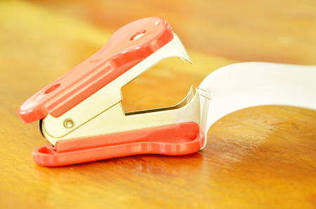 staple remover pulling wire from paper on wooden table Stock Photo